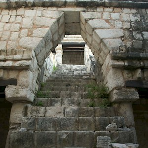 The distinctive Mayan arch beckons up a steep stairway on this temple under restoration at Chichen Viejo. <a href=></a>