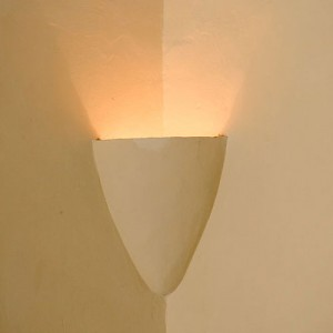 In early hacienda construction, plaster sconces were sculpted into the corners of walls, up high near the ceiling. They held torches, candles or oil lamps. This modern version uses electricity. <a href=></a>