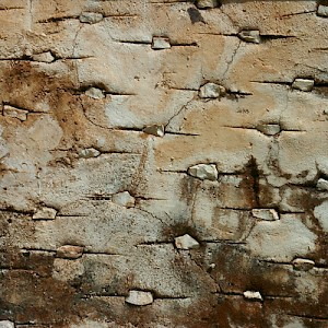 On many perimeter walls, a trowel is used to create a pattern that is filled with small stones, as on this aged chichum wall. <a href=></a>