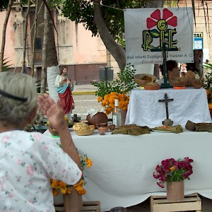 Una vieja (old woman) crosses herself while gazing at a Hanal Pixán altar in the Plaza Grande in Merida. <a href=></a>