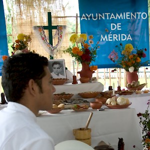 A young man in traditional Yucatecan costume sits in front of the Ayuntamiento&#039;s official Hanal Pixán altar. <a href=></a>