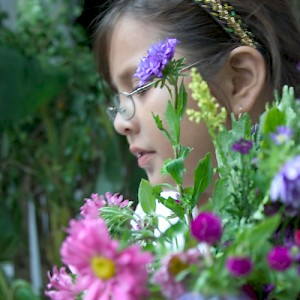 A young girl carrying flowers. <a href=></a>