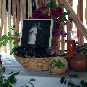 Mucbil Pollo wrapped in banana leaves sits in a basket in front of a photo of a married couple, long since passed away. <a href=></a>